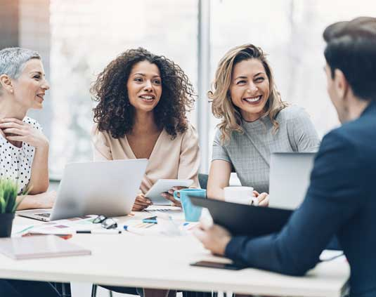 Three women conduct an interview for an open creative executive staffing position
