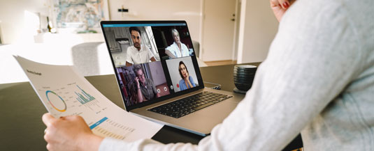 A virtual meeting with a coworker hired through Scion Remote Creative Staffing. We see the coworkers arm holding a paper with charts, and her laptop open with four creative team members on screen.