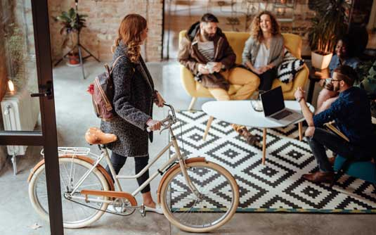 A newly hired temporary creative worker wheels her bike into the office and is greeted by her new coworkers