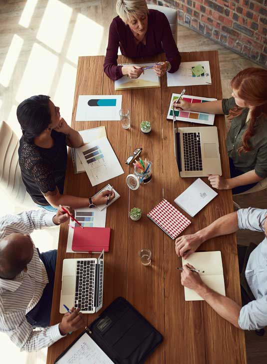Overhead view of creative temporary staff listing to their boss at a conference table