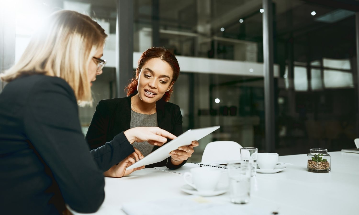 Two creative women sitting at an office table looking over paperwork. Creative Staffing Blog