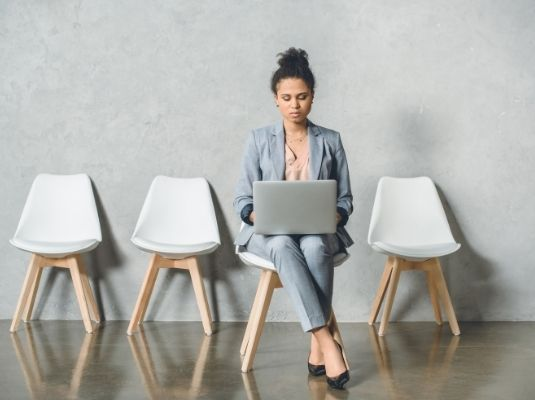 Woman sitting in a row of white chairs looking up agency on her computer