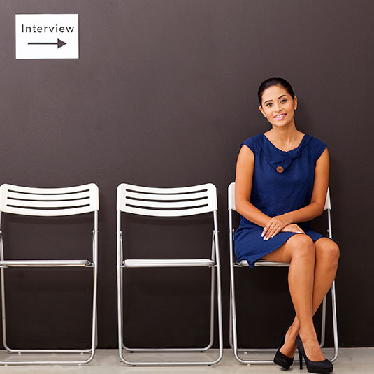 Image of women sitting in a witing room dress professionally in a blue dress below a sign that says interview
