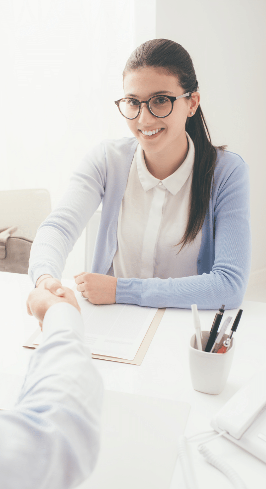 woman sitting at a table, shaking hands at job interview.