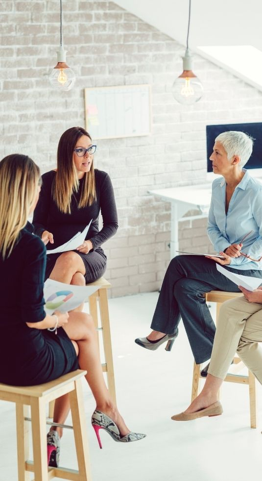 Women sitting at benches in a marketing meeting
