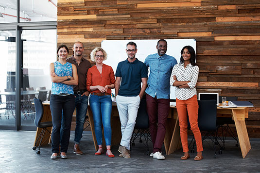 Six people (a diverse group) are standing in front of a wood wall who are staff from Scion and smiling