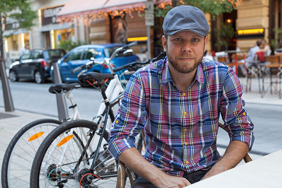 Staff member outside and seated near bikes and wearing a hat and smiling