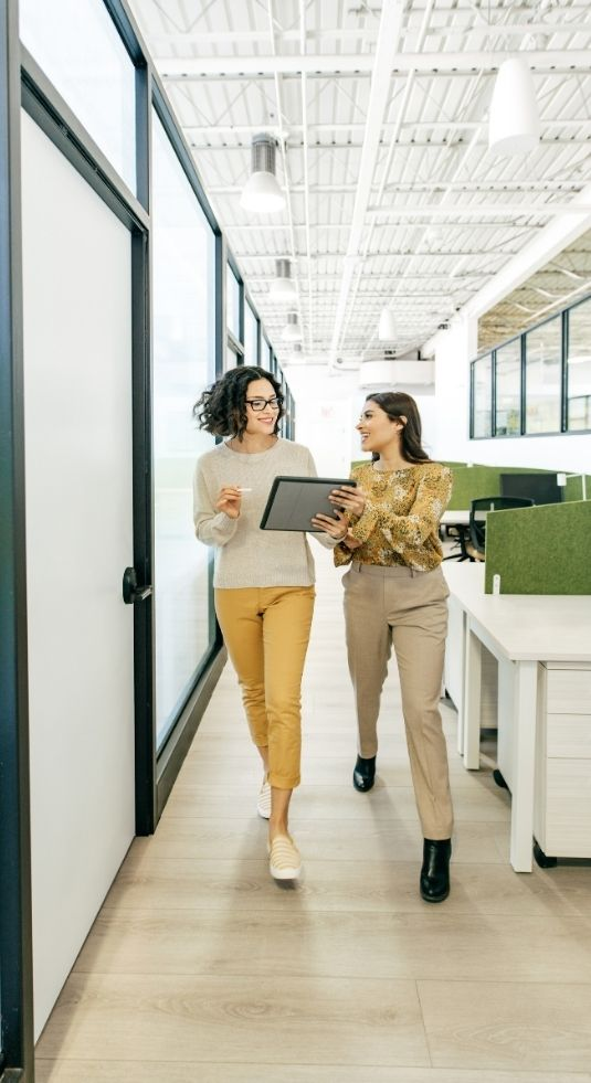 Two women in a nonprofit office walking down the hall