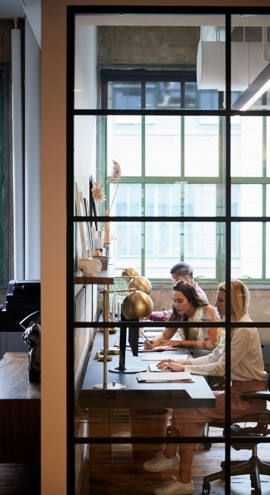Finance office - view of three people working at a desk through a glass divider.