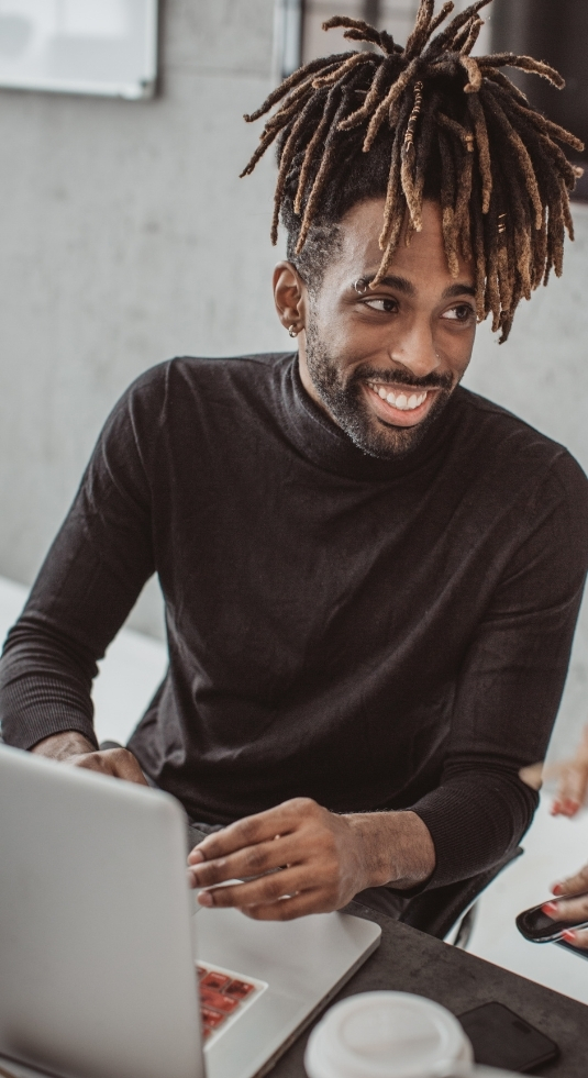 African American man working on nonprofit IT staffing at his computer desk.