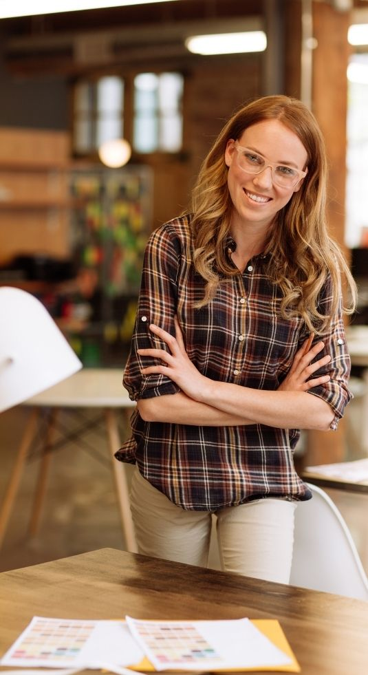 Women in a plaid shirt standing over a desk in a marketing department