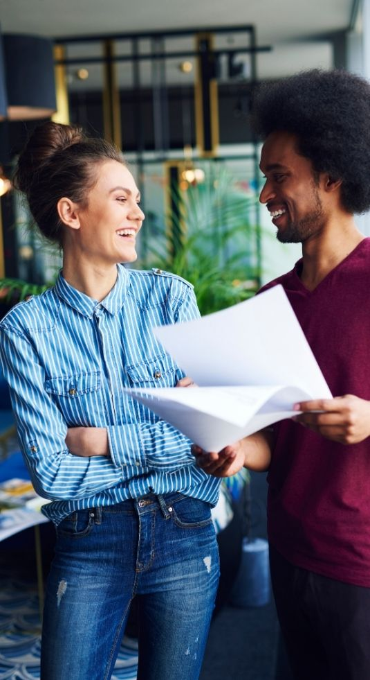 A woman & man standing in an open office - with plants in the background - laughing and discussing nonprofit human resources.