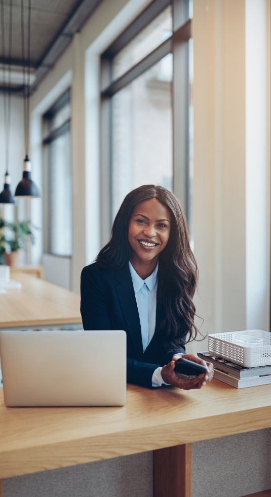 African American woman looking at camera, smiling and leaning over a tall desk with a laptop.