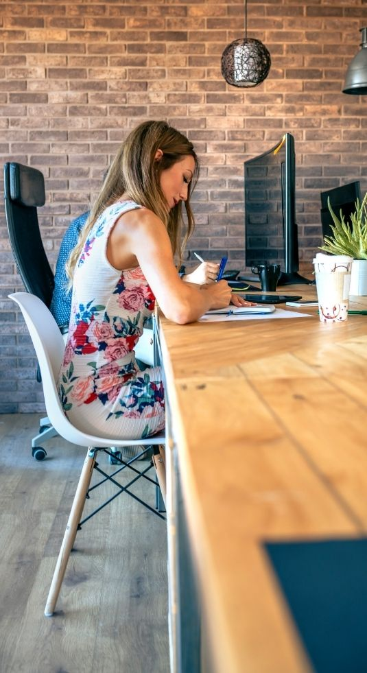 Woman in a floral dress sitting at a desk writing notes on nonprofit development staffing.