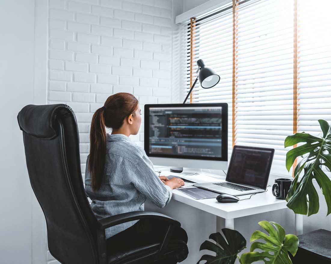 A technical staff member works remotely from her home office, writing code