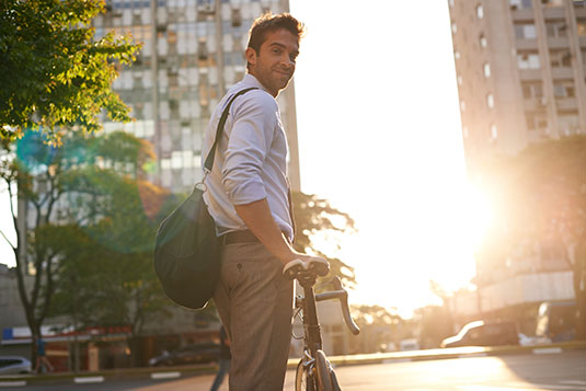 Image of Person About To Ride A Bike with the sun behind them and smiling