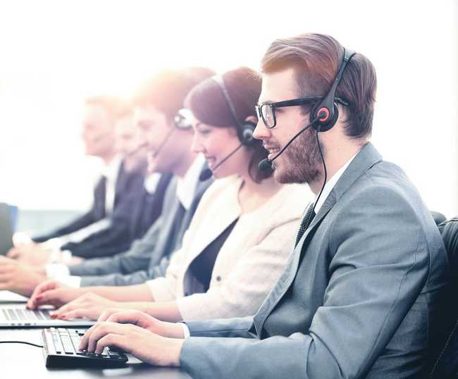 Image of Customer Service Call Center staff at work. Five people seen on the phone.