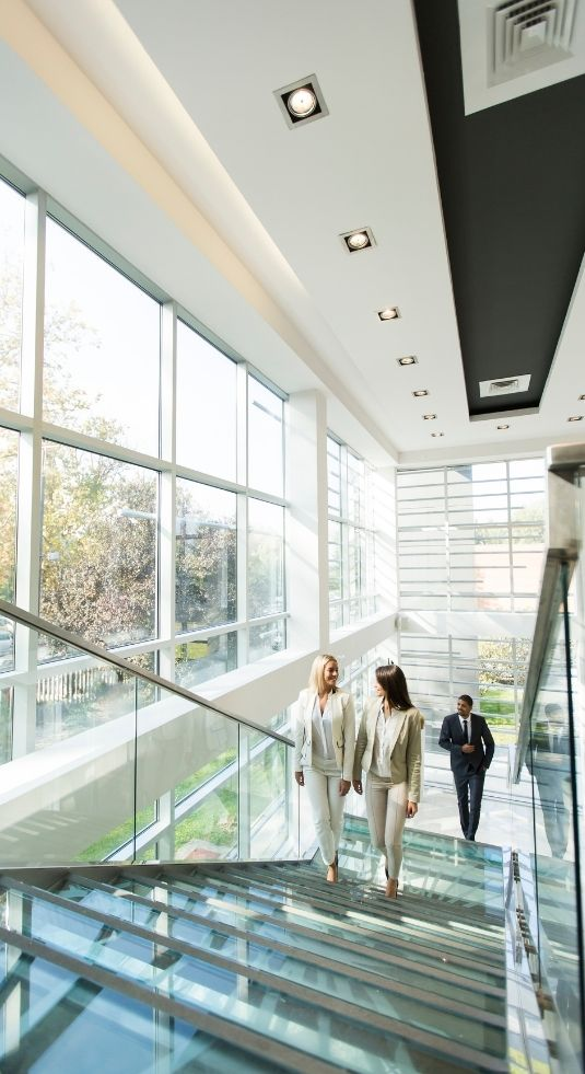 Two women walking up a corporate staircase with open windows to one side.