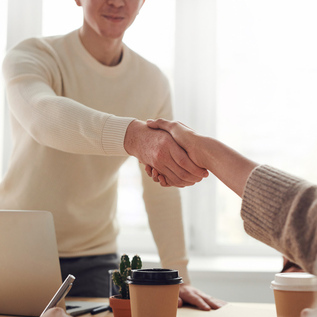 Two people shaking hands at a job interview.