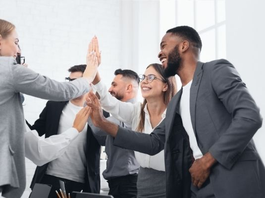 Team of coworkers celebrating a win by a group high five. Pictured are men and women high fiving each other.