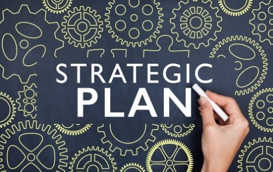 "Person writing ""Strategic Plan"" on a chalkboard."