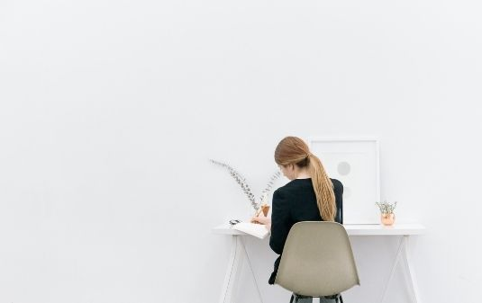 Women sitting at her desk with white background at her job search.