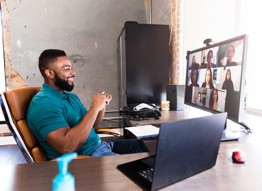 A remote worker has a virtual meeting with his team members